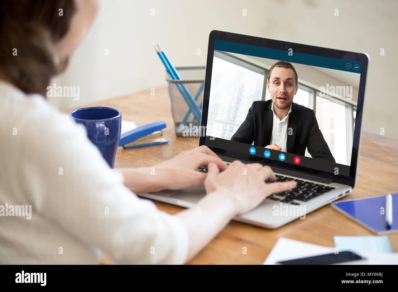 La empresaria hacer video llamada al socio de negocios con ordenador portátil. Vista trasera cerca de joven tener conversaciones con clientes corporativos. Jo remoto Imagen De Stock