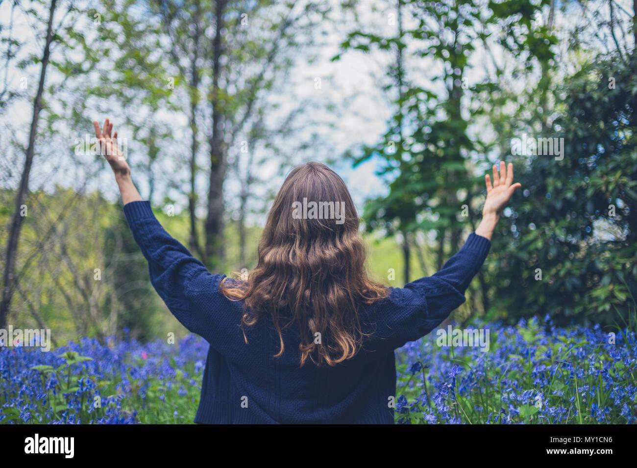 Un joven está sentado en una pradera de campanillas y es alegría levantando sus brazos Imagen De Stock