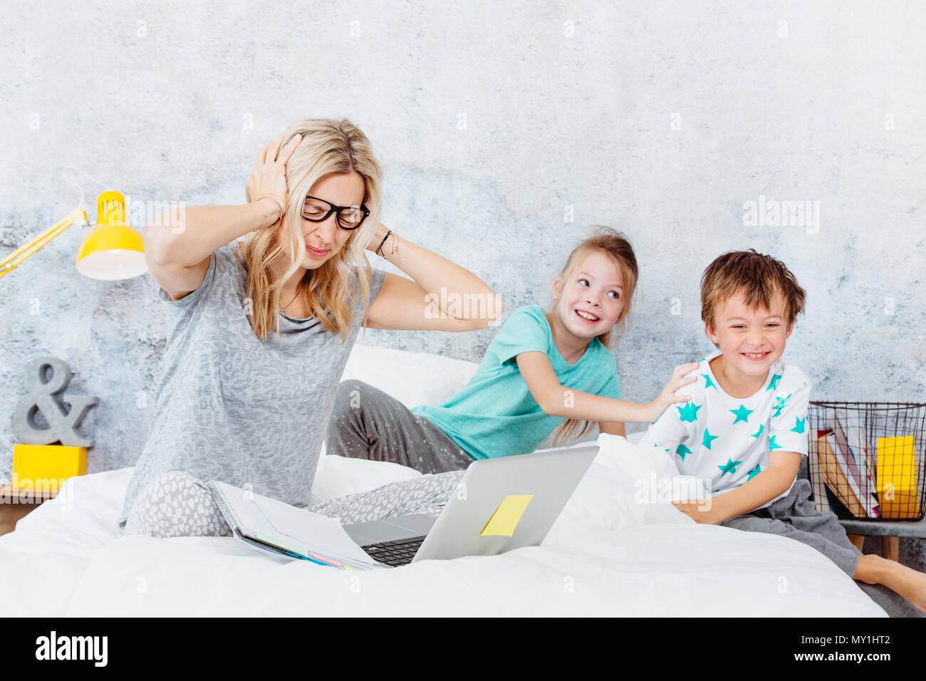 Business mum en el trabajo mientras sus hijos juegan en la cama Imagen De Stock