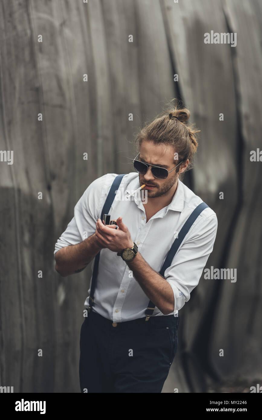 323a82bf96 Retrato de guapo elegante hombre barbado en gafas de sol y tirantes de  iluminación con encendedor de cigarrillos