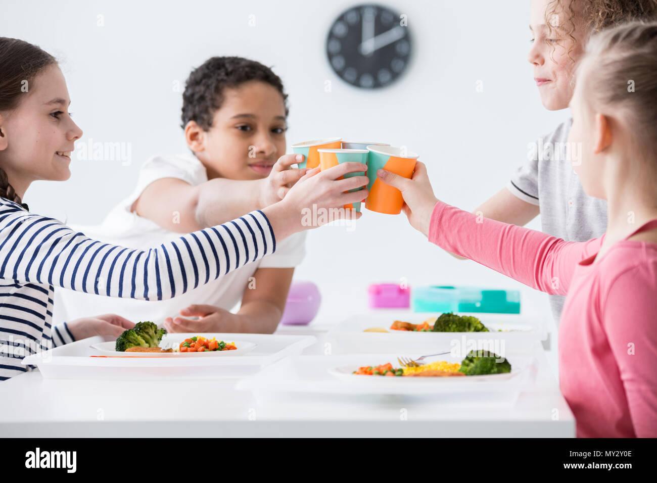 Los niños felices haciendo un brindis durante la fiesta de cumpleaños de un amigo en casa Imagen De Stock