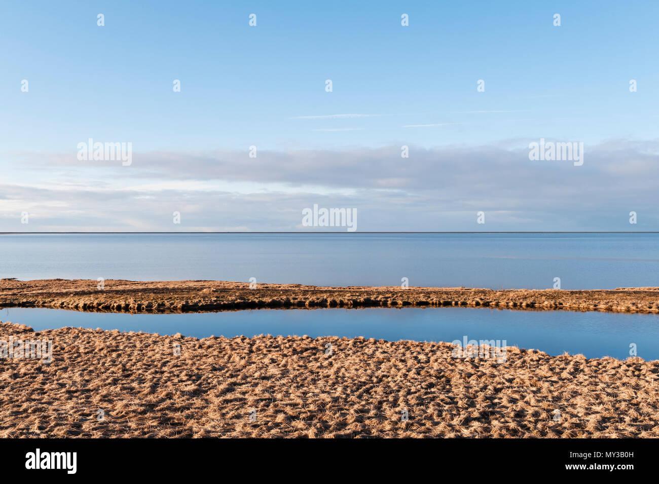 El sur de Islandia. La tranquila laguna de marea Holtsós, justo al sur de Eyjafjallajökull, visto temprano en la mañana desde la carretera de circunvalación Imagen De Stock