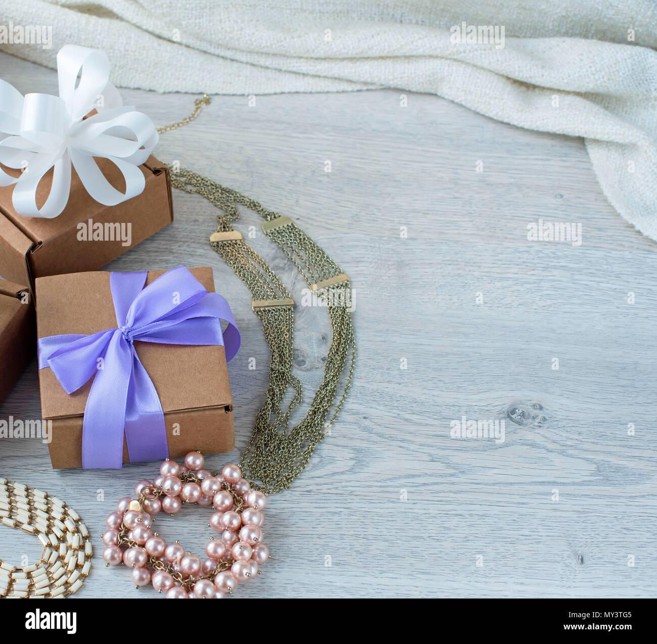 83973e34c70a Cajas de regalo con regalos. Joyería de mujeres sobre un fondo de madera  ligera.