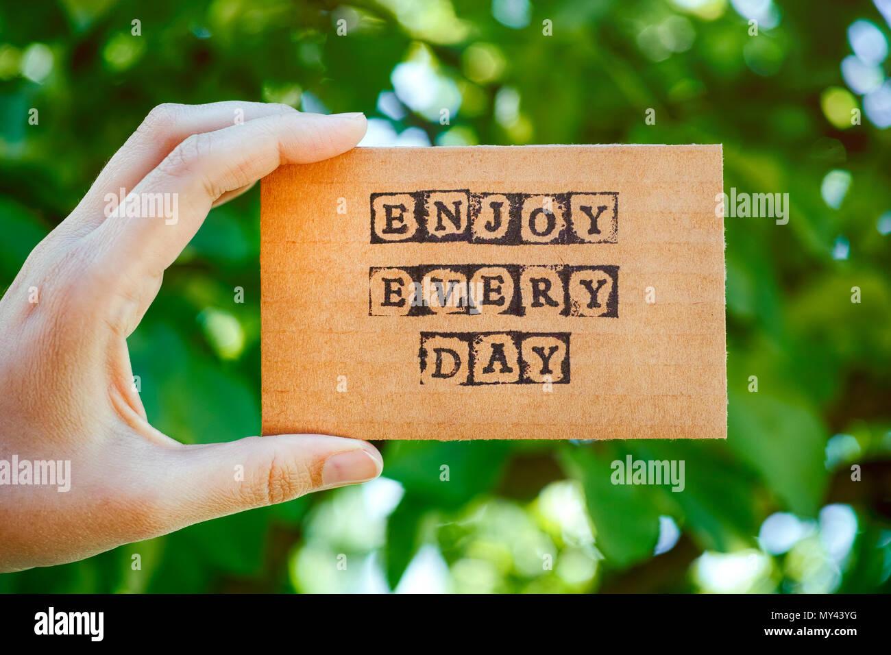 Mujer mano sujetando la tarjeta de cartón con palabras disfrutar cada día hechas por sellos alfabeto negro contra el fondo verde de la naturaleza. Imagen De Stock
