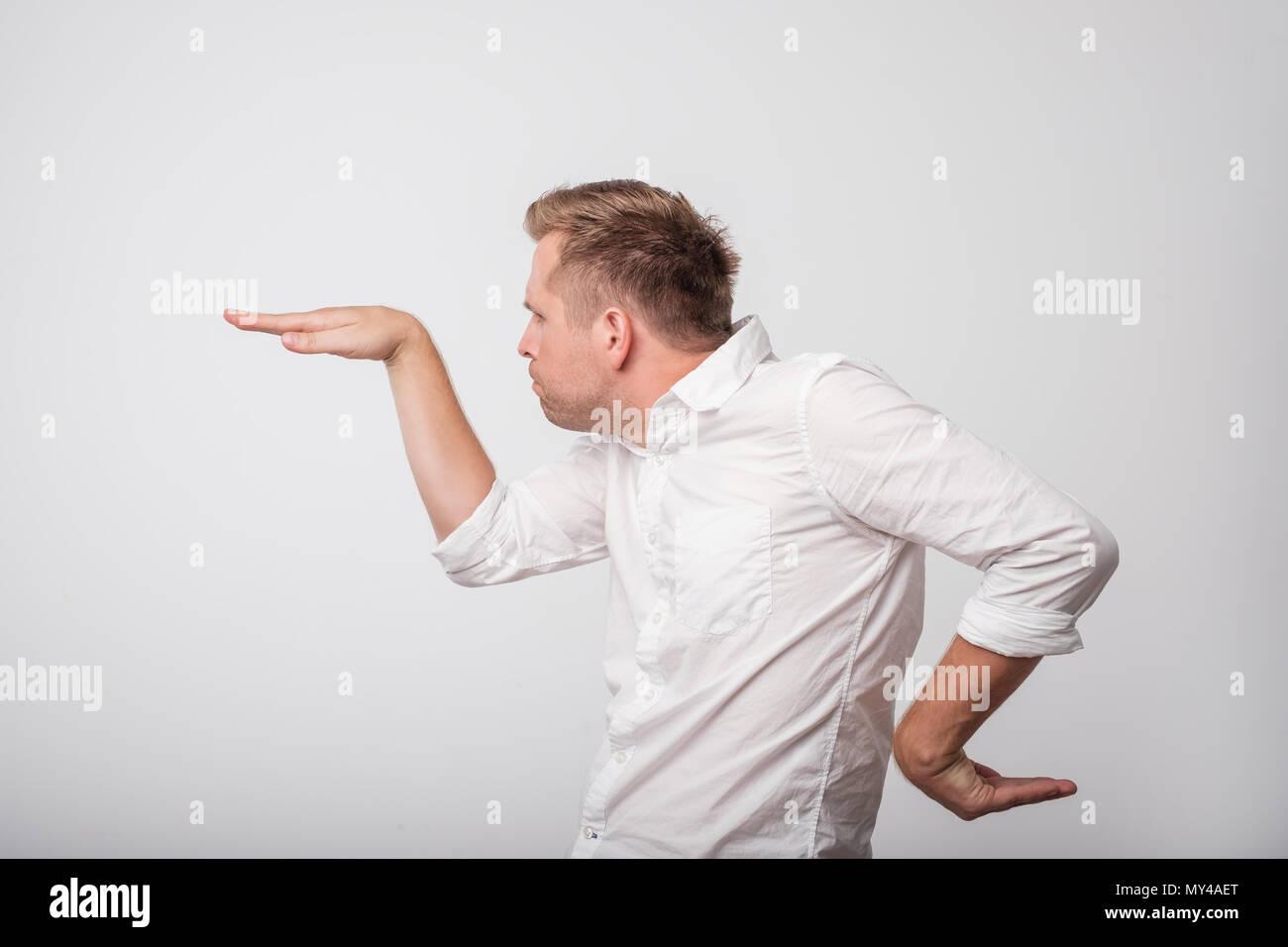 Caucasian emocionado joven levantando sus manos en una vista lateral como él bailando. Imagen De Stock