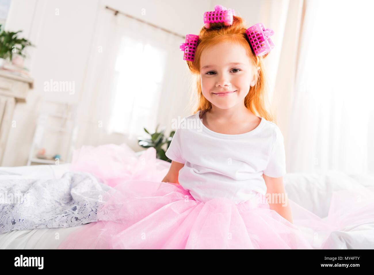 14b596881 Retrato de niña sonriente con rulos en la cabeza y falda tutú de tul  mirando a la cámara · LightField Studios Inc. / Alamy Foto de stock