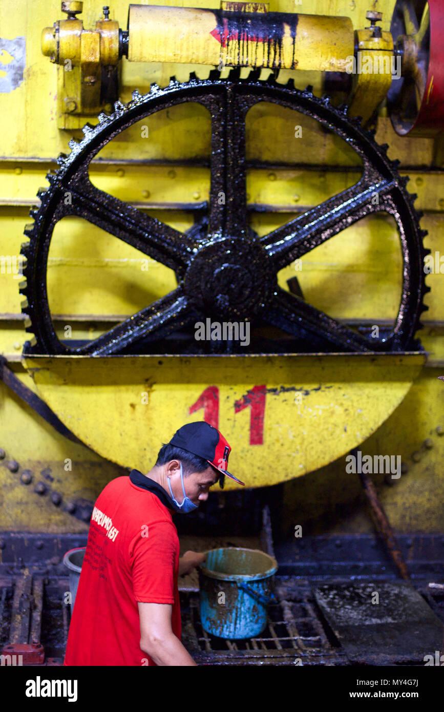 Un trabajador haciendo trabajos de mantenimiento durante la producción de caña de azúcar de caña Tasikmadu Mill en Java Central, Indonesia. © Reynold Sumayku Imagen De Stock