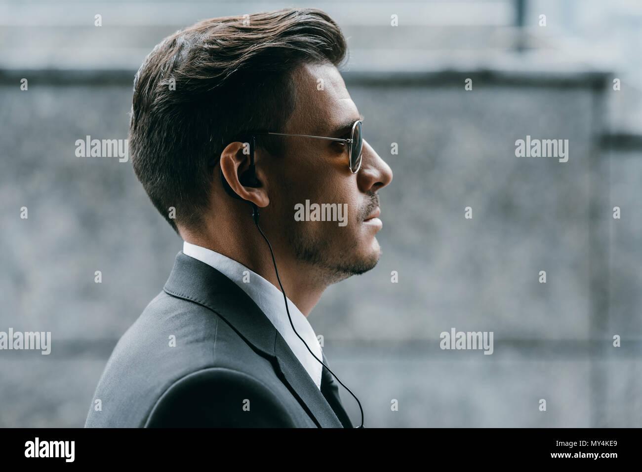 Perfil de guardaespaldas guapo con gafas de sol y seguridad auricular Foto de stock