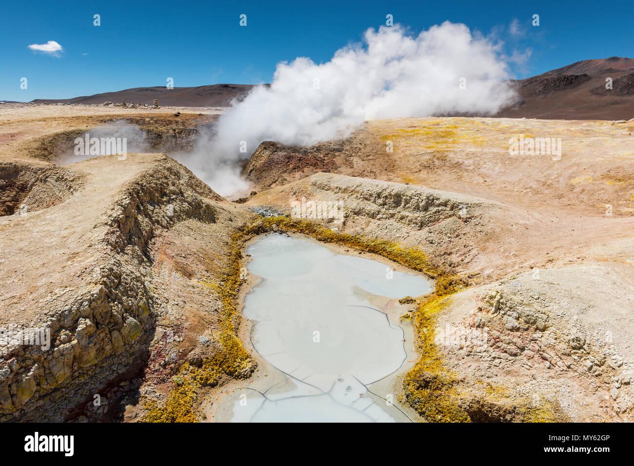 La actividad volcánica de Sol de Mañana en Bolivia entre Chile y el Salar de Uyuni. Las piscinas de lodo y fumarolas con vapor de agua, senderos en la Cordillera de Los Andes. Imagen De Stock