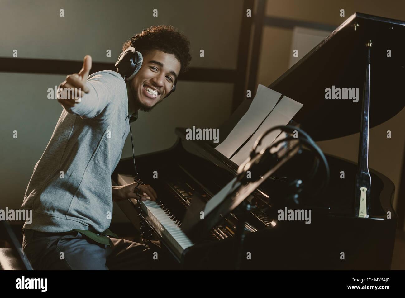 Feliz joven pianista mostrando pulgar arriba Imagen De Stock