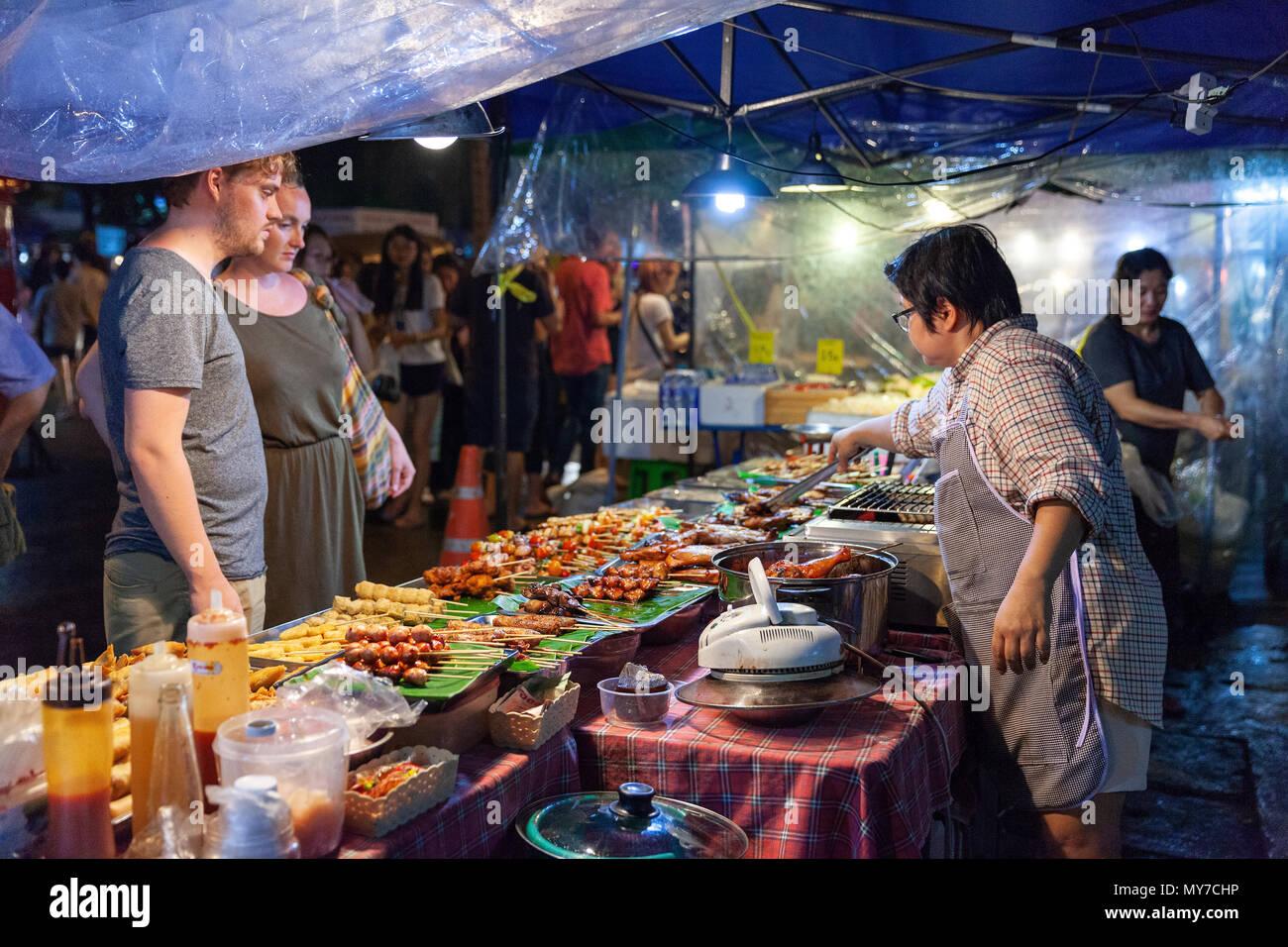 CHIANG MAI, Tailandia - 27 de agosto: Pareja compra comida callejera tradicional tailandés en el mercado del sábado noche, (Calle) el 27 de agosto de 2016 en Chiang Imagen De Stock