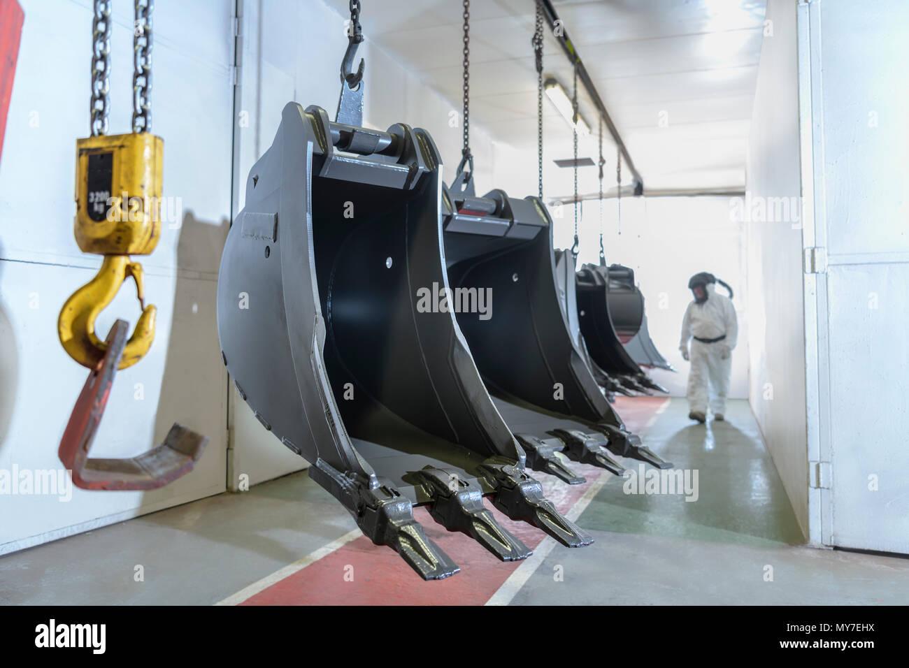 Pulverizador de pintura comprobación pintados digger baldes en fábrica de ingeniería Foto de stock