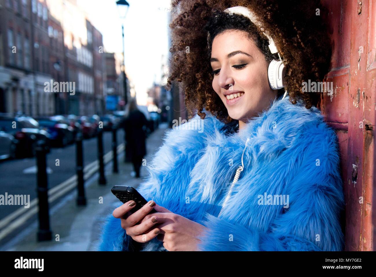 Retrato de mujer con el cabello afro vistiendo abrigo de pieles, escuchando música a través de auriculares en smartphone Foto de stock
