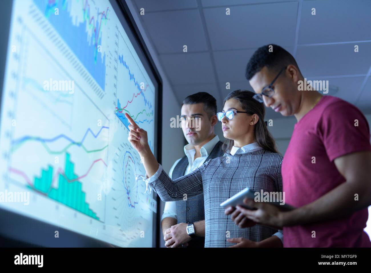 Equipo empresarial ver gráficos y gráficos de pantalla interactiva en reunión de negocios Foto de stock