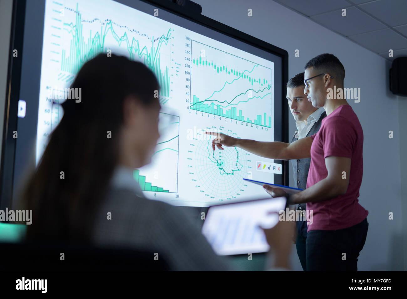 Equipo empresarial ver gráficos y gráficos de pantalla interactiva en reunión de negocios Imagen De Stock