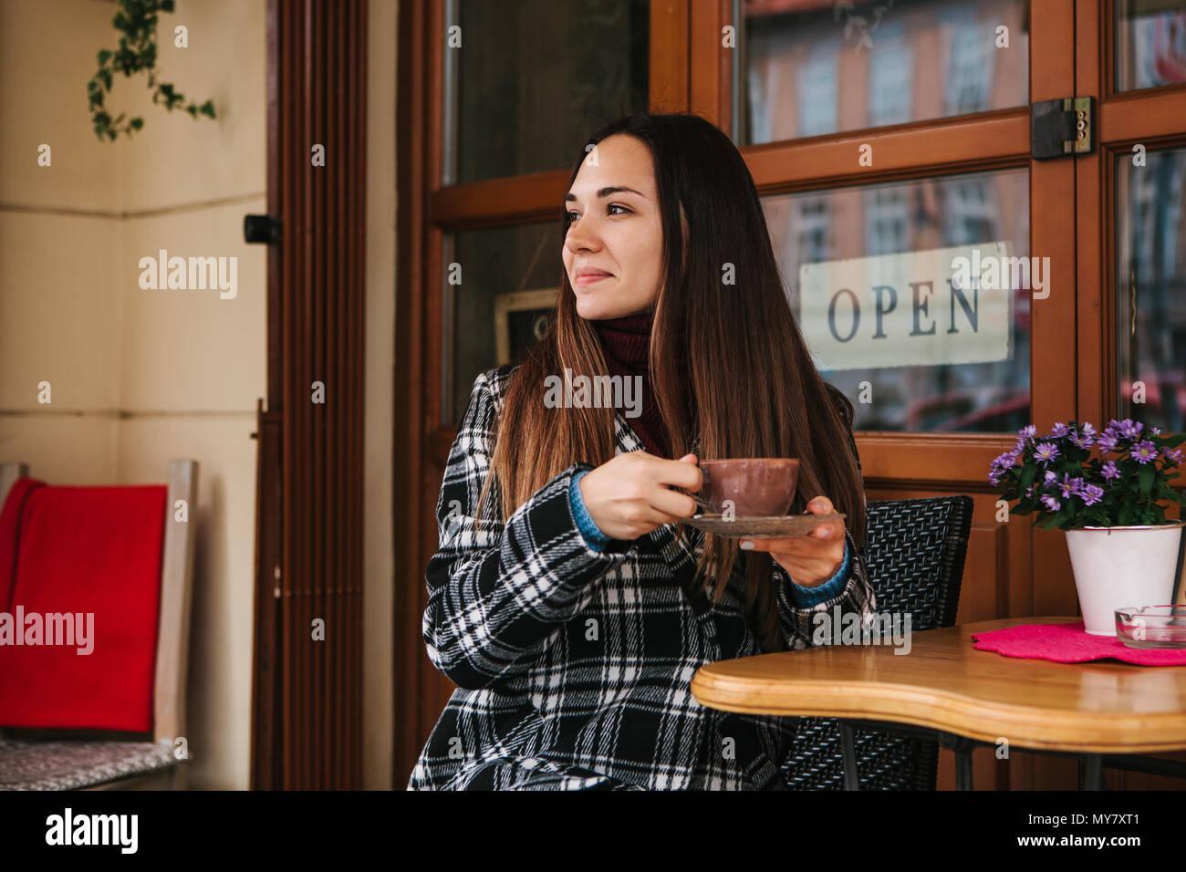 Hermosa joven bebidas de café o chocolate caliente en una cafetería de la calle Imagen De Stock