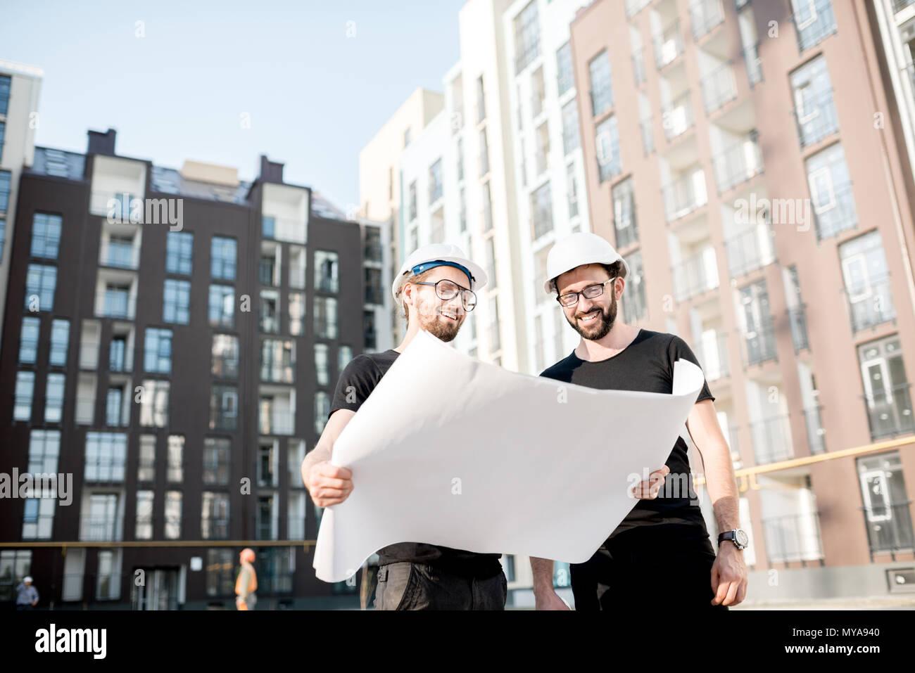 Constructores con dibujos en la zona residencial de nueva construcción Foto de stock