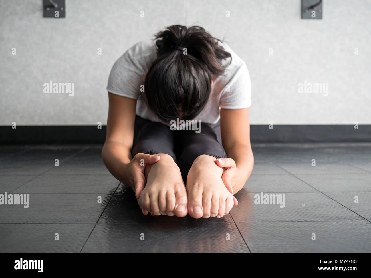 Joven realizando y sentarse y llegar a estirar el tendón de la corva y aumentan la flexibilidad. Imagen De Stock