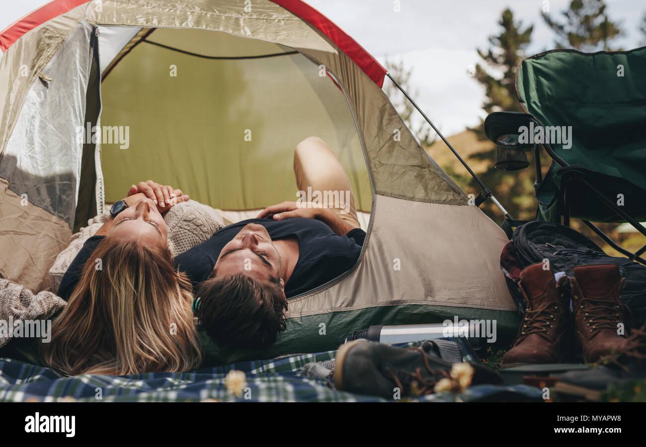 El hombre y la mujer yaciendo juntos en la tienda. Pareja durmiendo en una tienda de campaña en el camping. Imagen De Stock