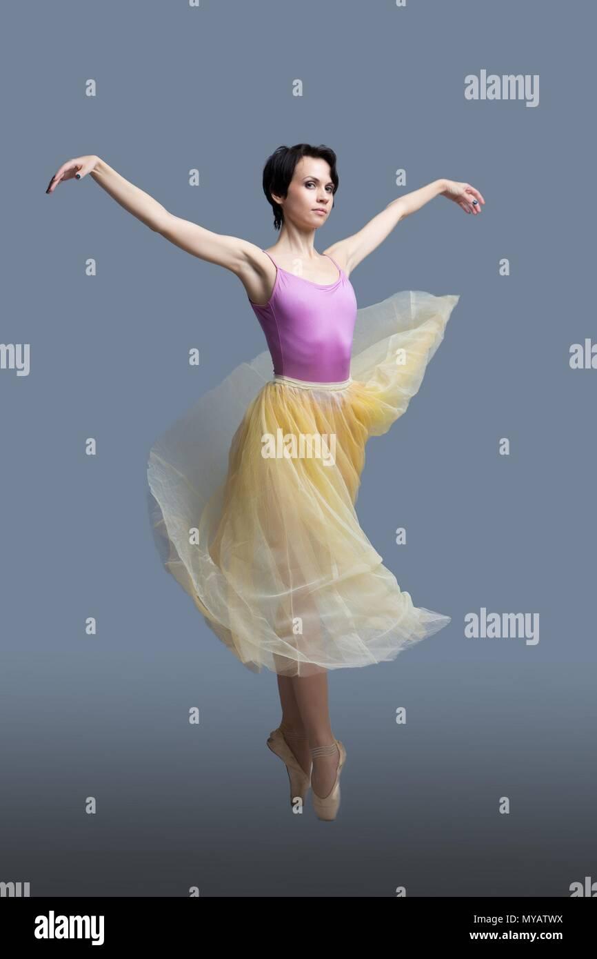 Bailarina está bailando en el estudio sobre un fondo gris Imagen De Stock
