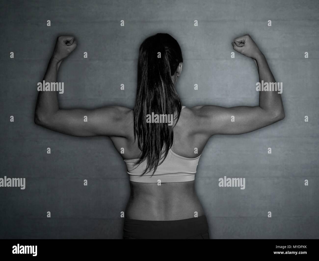 Mujer joven en deportes top flexionando los músculos, vista trasera. Imagen De Stock