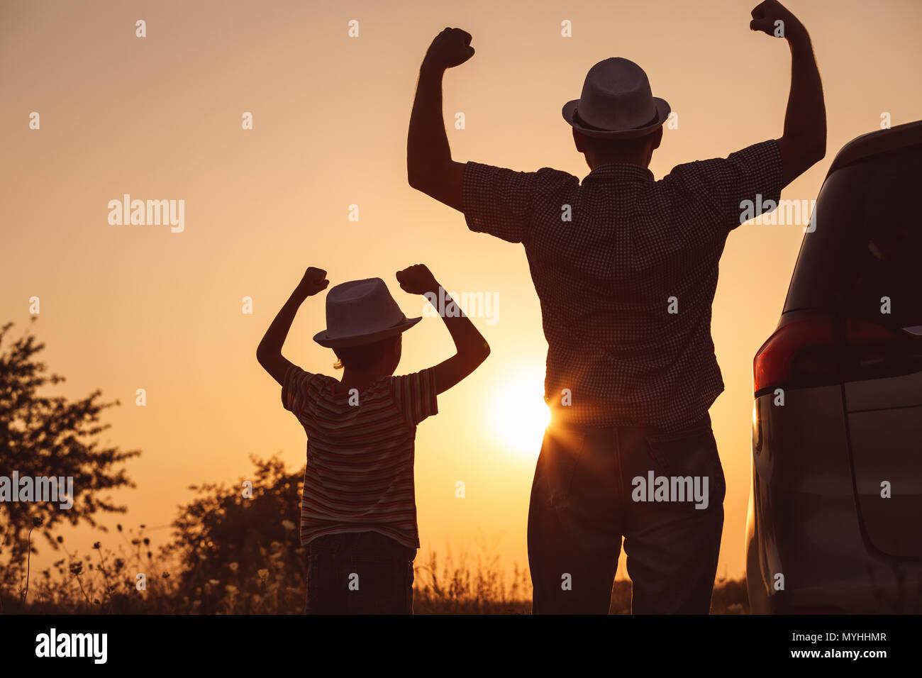 Padre e hijo jugando en el parque a la hora del atardecer. La gente divirtiéndose en el campo. Concepto de familia y de vacaciones de verano. Imagen De Stock