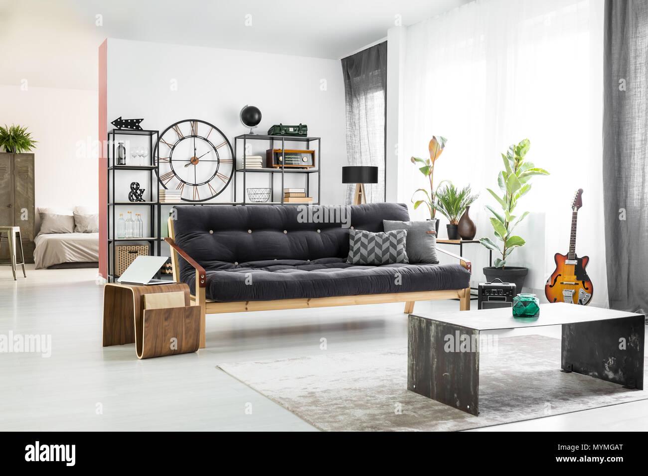 Florero Verde Oscuro Delante De Un Sofa Y Mesa De Madera Con Un