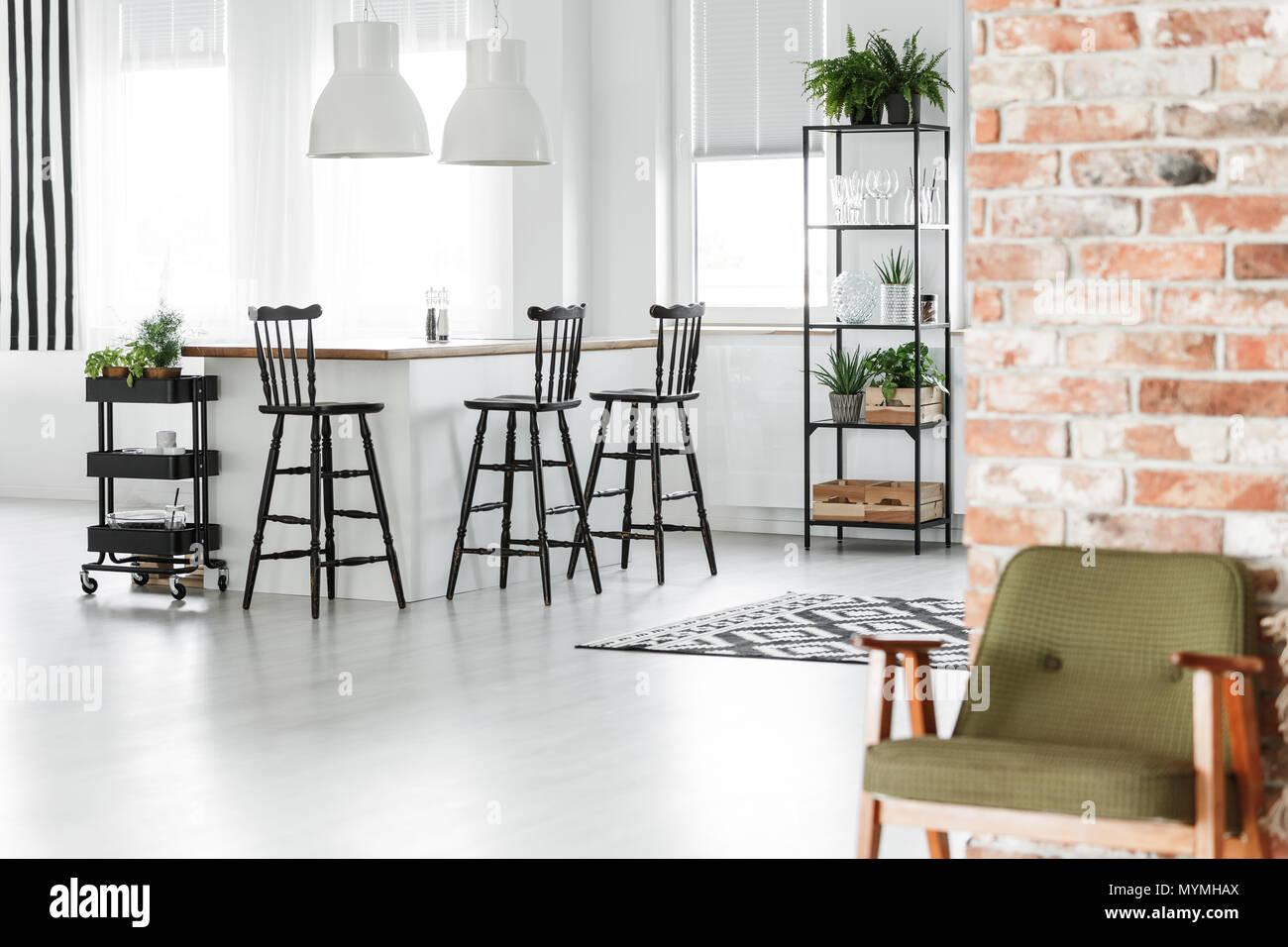 Retro sillón verde contra la pared de ladrillo rojo con negro en la habitación y la isla de cocina, taburetes Foto de stock