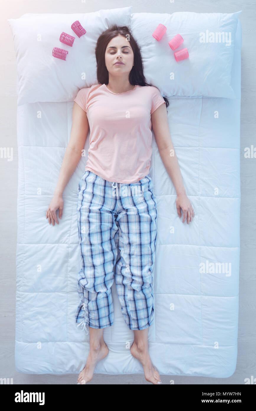 Bella mujer durmiendo con rizadores de pelo en la almohada Imagen De Stock