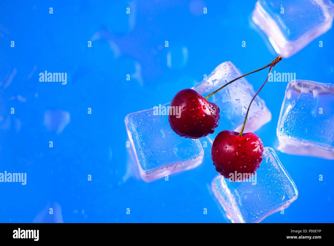 Las cerezas frescas sobre una pila de cubos de hielo de cerca en un fondo azul brillante. Concepto de bebida refrescante de verano con espacio de copia Imagen De Stock