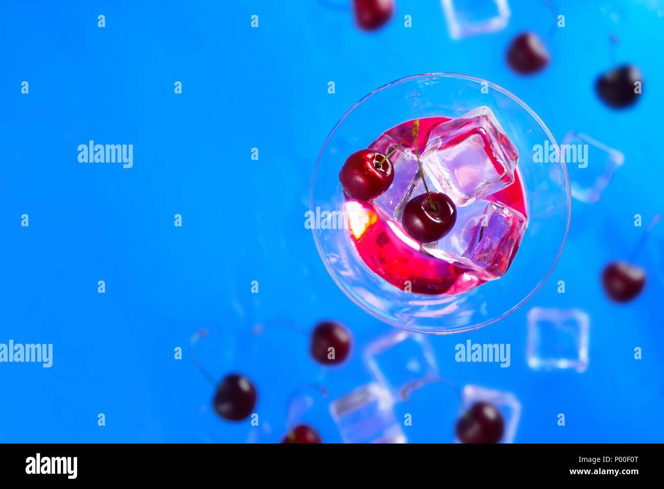 Licor de cereza de cóctel de cristal sobre un fondo azul. Refrescante bebida fría laicos plana con espacio de copia Foto de stock