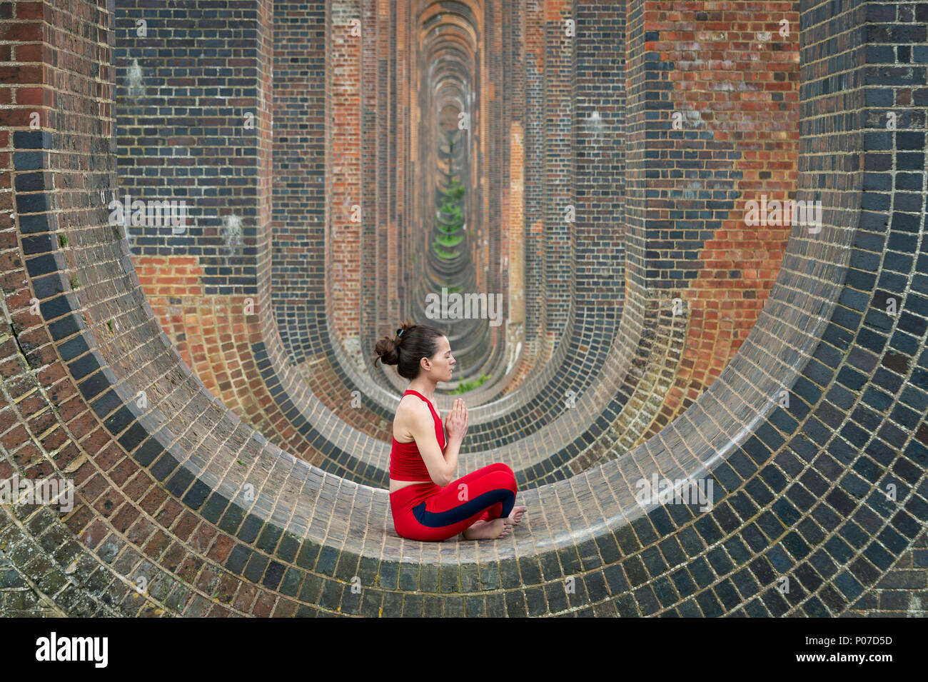 Mujer sentada en los arcos del viaducto del Valle Ouse practicando yoga y meditación Imagen De Stock