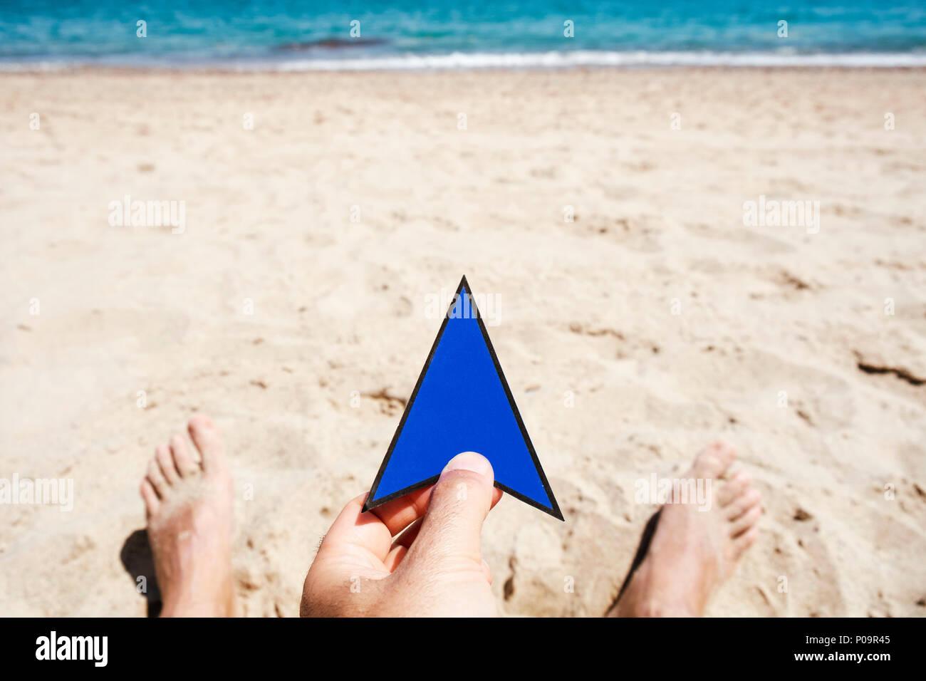 Primer plano de un joven hombre caucásico con una flecha azul señal en su mano, relajándose en la playa, con el mar de fondo Imagen De Stock