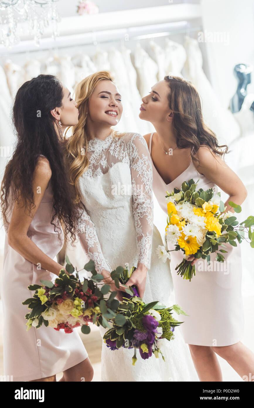 05a189624 Las mujeres atractivas en vestidos de novia besándose en salón de bodas