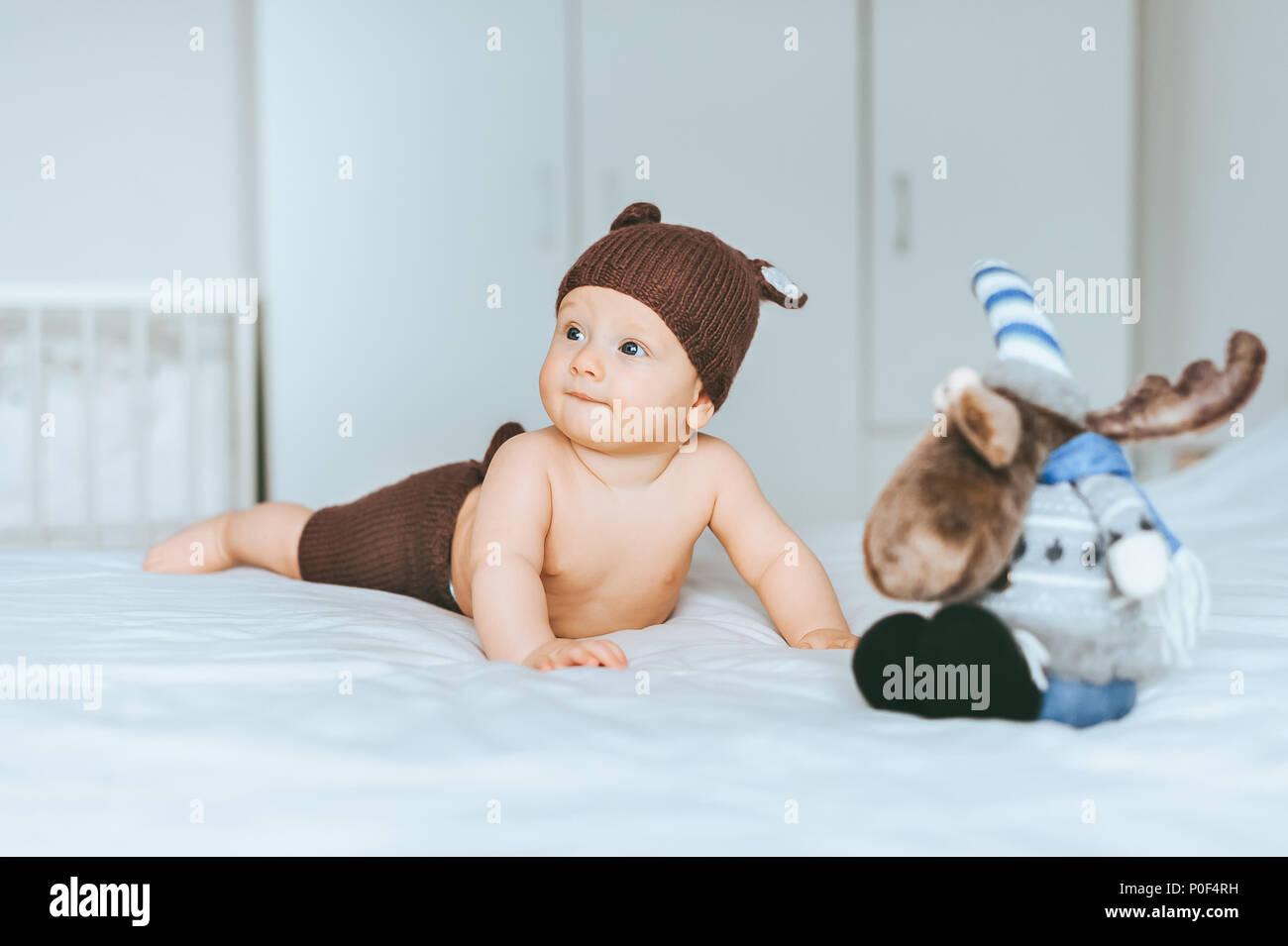 Adorable bebé niño en tejido deer cortos y sombrero en la cama con alces  juguete 1153b61de9d