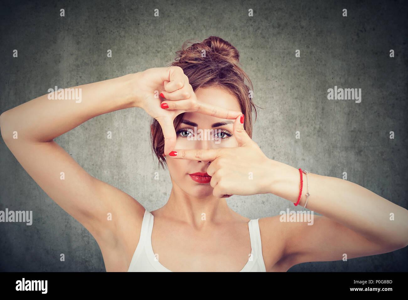 Joven haciendo el bastidor con los dedos y mirando a través de límites en la cámara sobre fondo gris Imagen De Stock