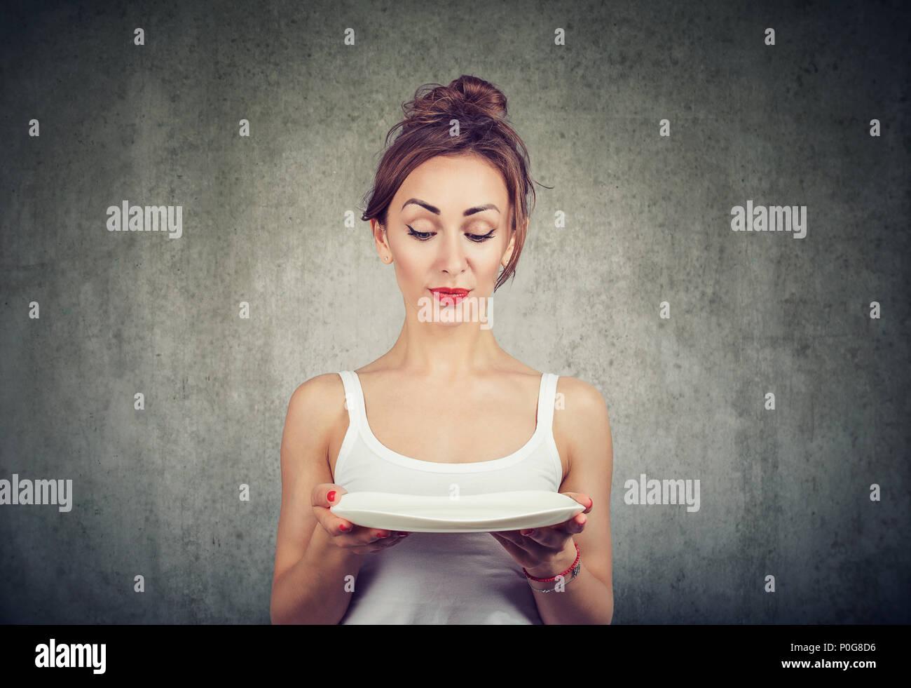 Flaco joven chica sujetando la placa de vacío y buscando dudoso con las restricciones de dieta de pie en gris Imagen De Stock