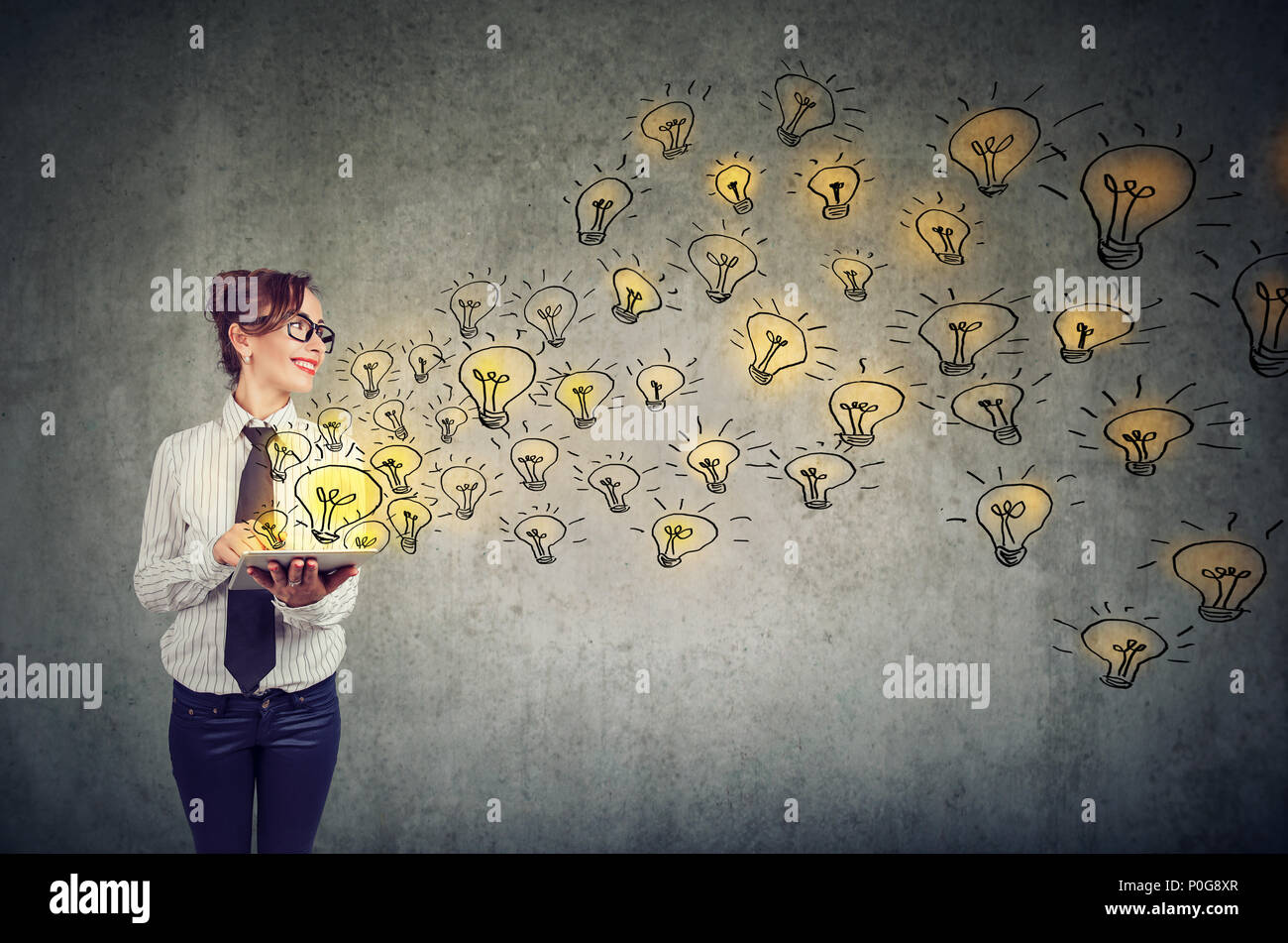 Vista lateral de la joven mujer de negocios la celebración de tablet pc con ideas brillantes Imagen De Stock
