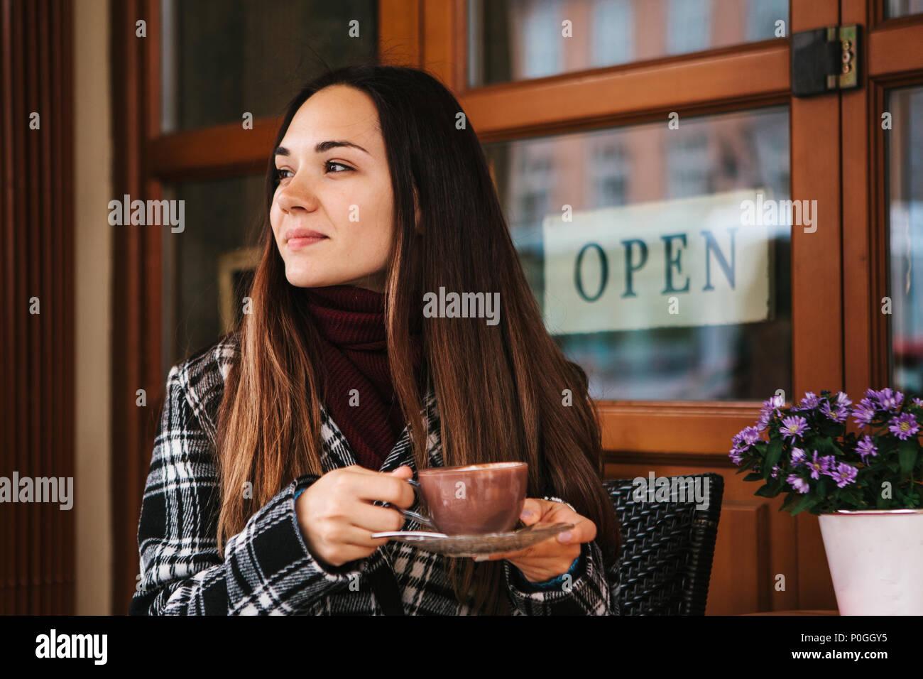 Hermosa joven bebidas de café o chocolate caliente en una cafetería de la calle Foto de stock