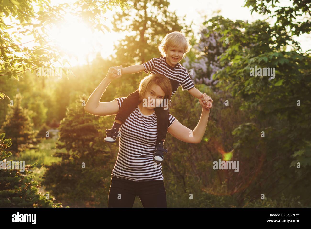 Madre e hijo en rayas T-shirts. Mujer sosteniendo boy en piggyback. La familia juntos. Divertirse Imagen De Stock