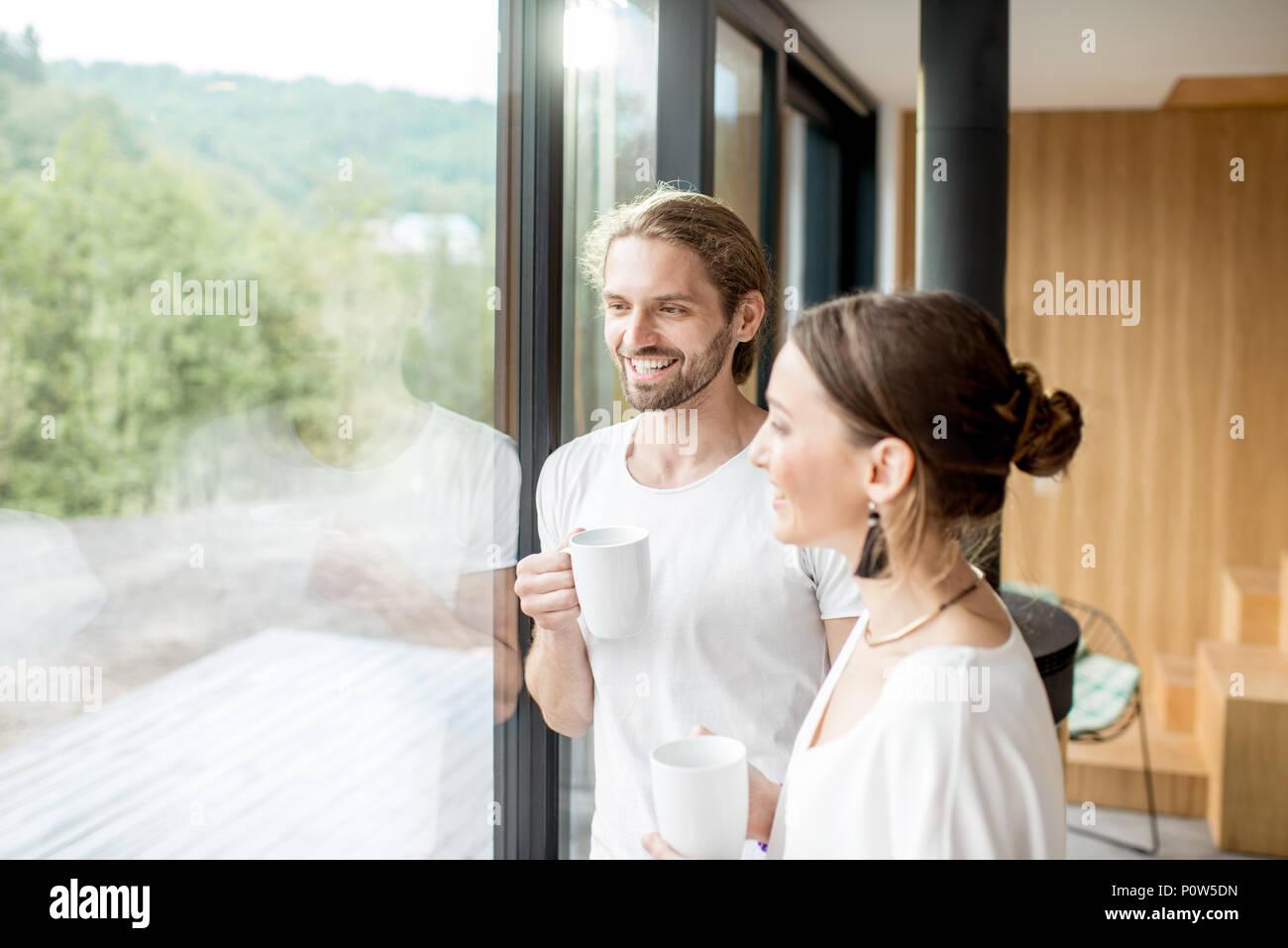 Par de pie cerca de la ventana interior Imagen De Stock
