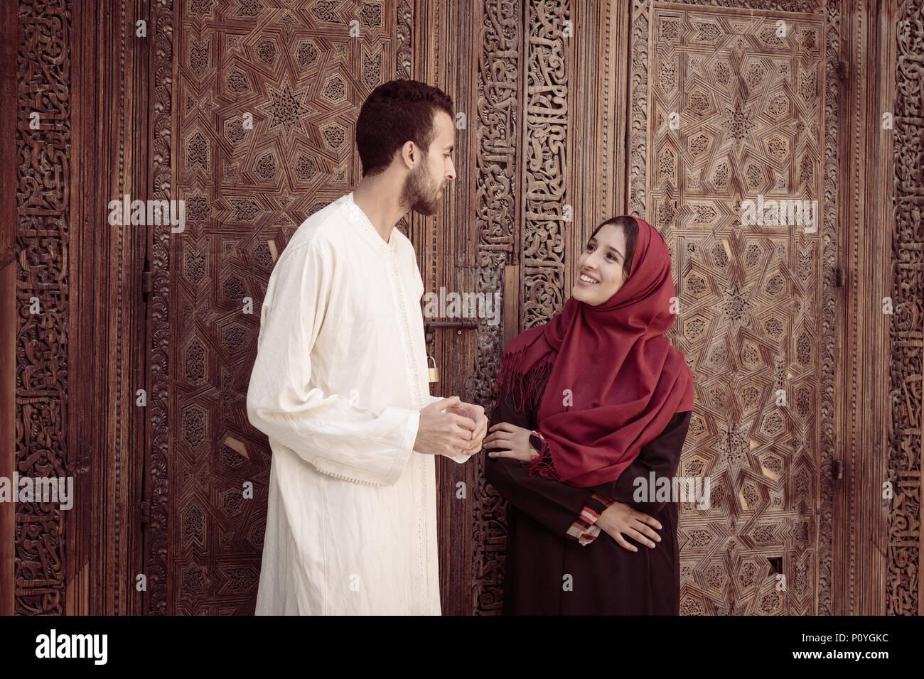 Joven pareja musulmana en relación hablando y sonriendo en ambiente árabe tradicional Imagen De Stock