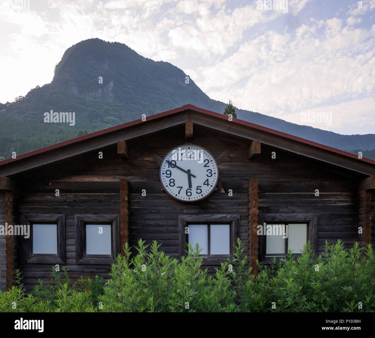dad05f646 Gran reloj pequeño edificio de madera en la parte delantera de alta montaña  en el momento de la 5:50 de la tarde