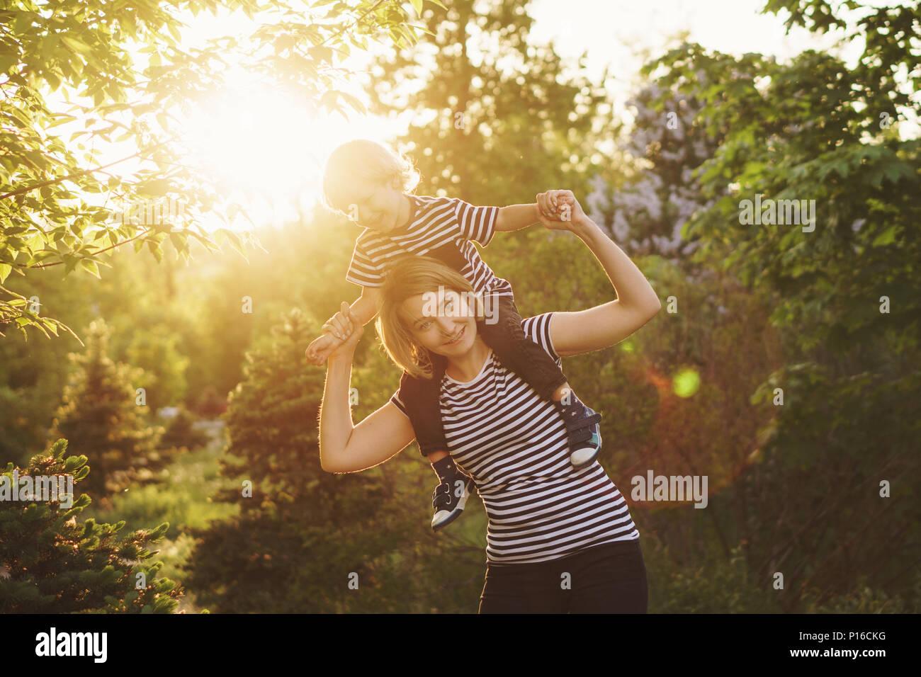 Madre e hijo en rayas T-shirts. Mujer sosteniendo boy en piggyback. La familia juntos. Divertirse. En Sunset Park Imagen De Stock