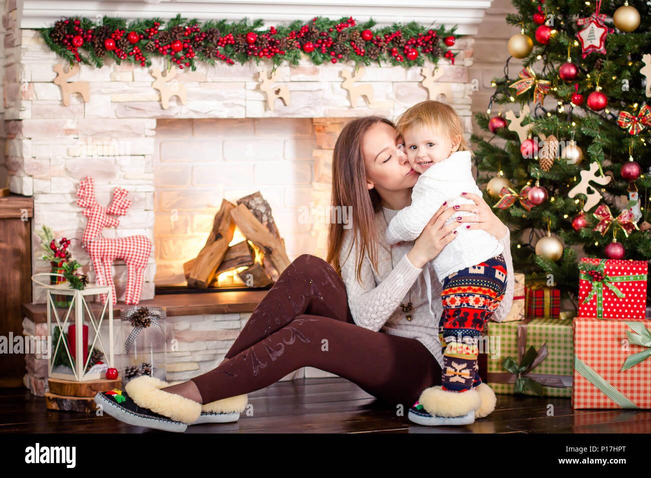 Una joven madre con una hija pequeña para sentarse cerca de la chimenea y decorado árbol de navidad. Imagen De Stock