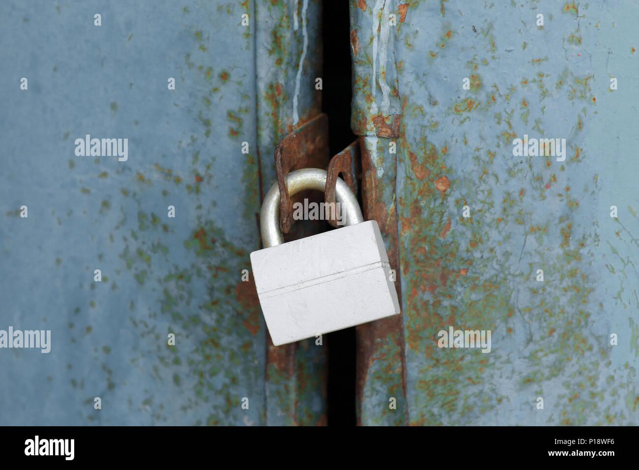 Nuevo candado cerrado sobre una antigua puerta de metal Foto de stock