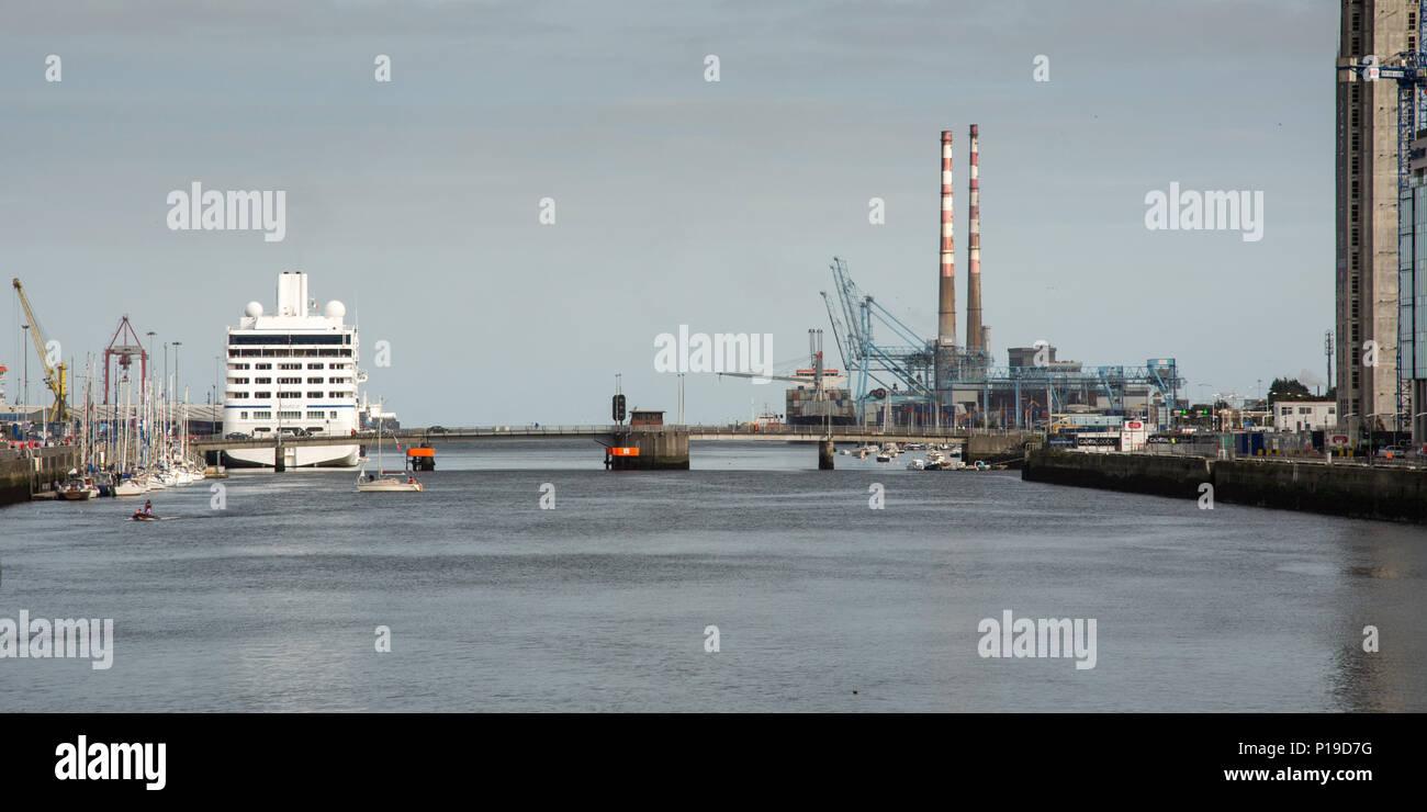 Los buques atracados en el puerto de Dublín en el estuario del río Liffey, con el hito de chimeneas de las Poolbeg Twin Power Station en el landsca industrial Foto de stock