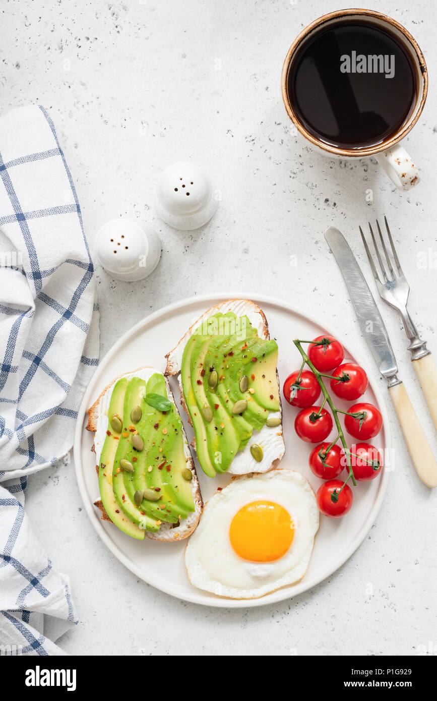 Tostada con aguacate, huevo frito, tomates y una taza de café negro americano en brillantes antecedentes concretos. Vista superior y espacio para copiar texto Imagen De Stock