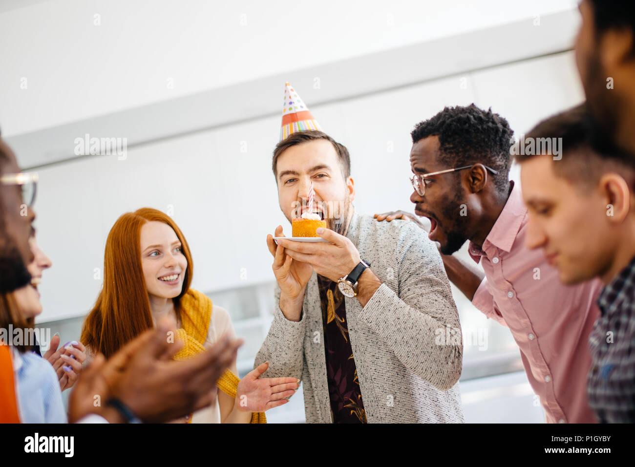 Codiciosos guy está tratando de morder una paz más grande de la torta en frente de amigos Imagen De Stock