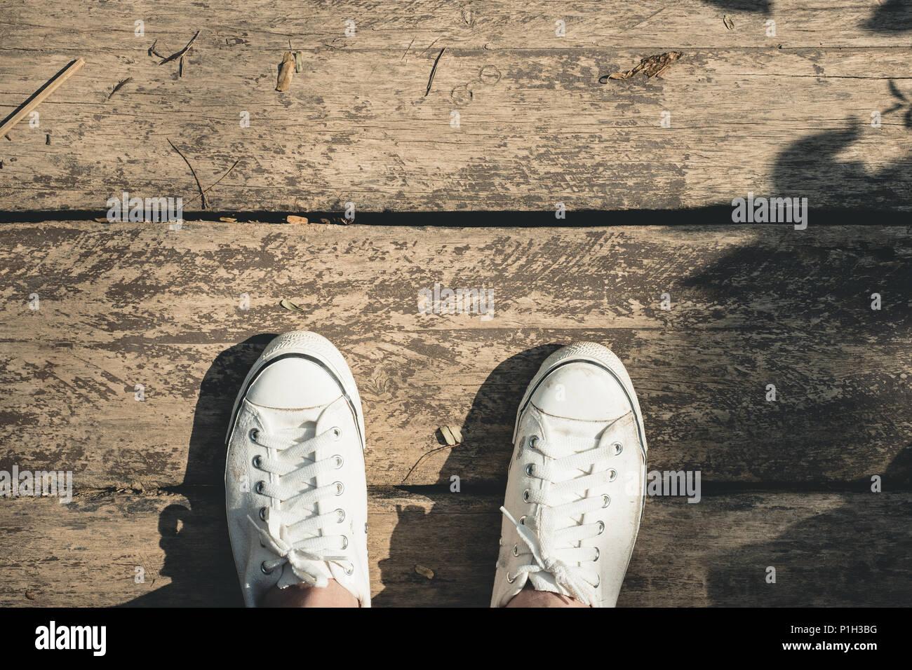 Vista aérea de zapatillas zapatillas de tela blanca de pie en el grunge  viejo piso de 0844a6edb565